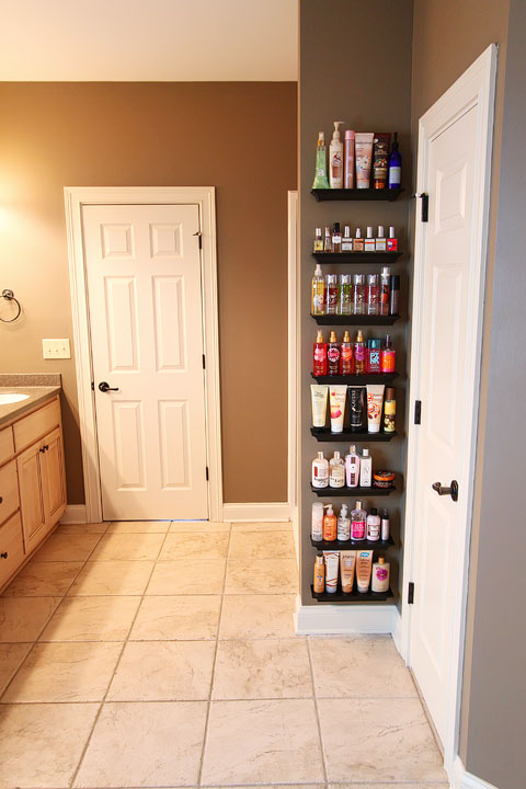 Easy DIY Bathroom Organization! Use crown molding to make shelves to organize perfumes, lotions, hairspray, etc. Neat, organized, and right at your fingertips! From kevinandamanda.com