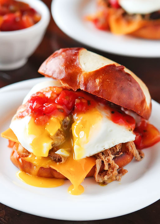"""Caribbean Pulled Pork Sandwiches. Spicy pulled pork topped with a sweet mango-peach salsa, a runny fried egg and served on a buttery pretzel bun. He took one bite and said, """"Can we have this again tomorrow night?"""""""