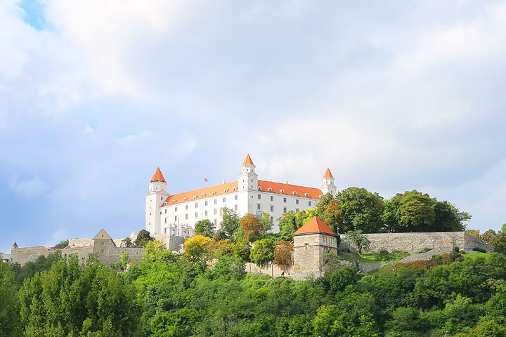 Fairytale castle with an orange roof high on a hill