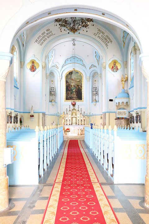 Inside of the Blue Church with a red carpet down the center aisle