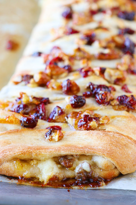 This beautiful Harvest Breakfast Braid is perfect for breakfast, brunch, or even dinner! Layers of sausage, apple, and havarti cheese make for the perfect sweet and salty combo. It's all topped with cranberries and pecans in a sweet orange marmalade glaze.