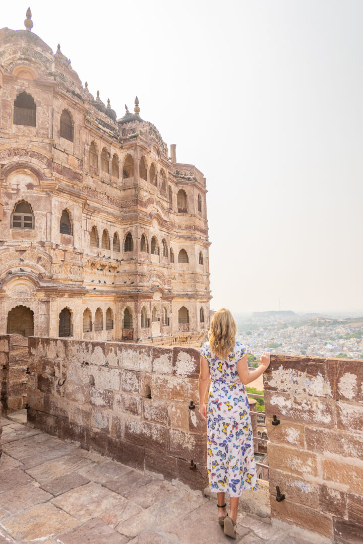 Woman looking over an old city wall in Jodhpur, India