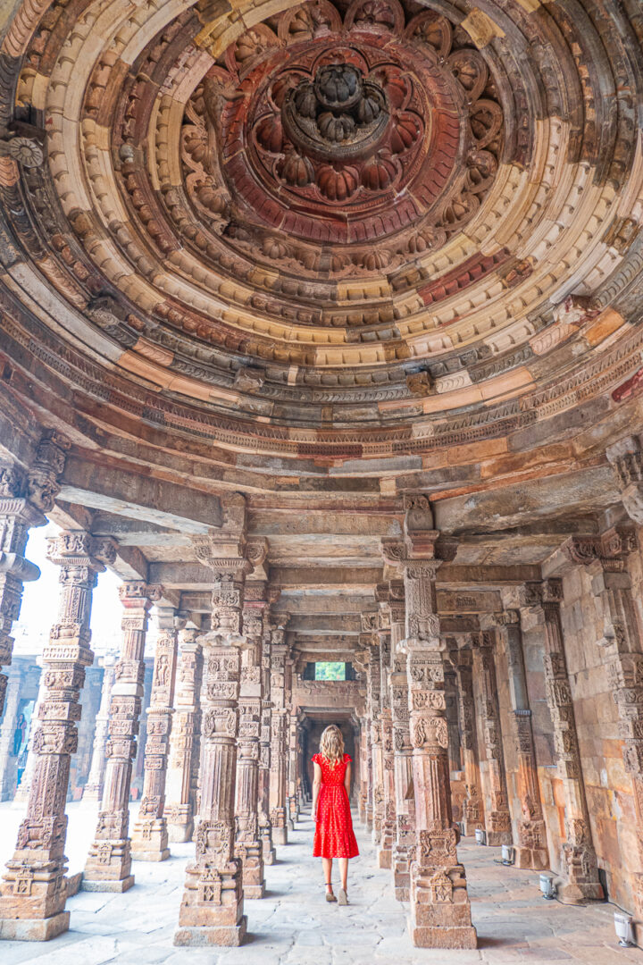 Girl in red dress at Qutub Minar in New Delhi