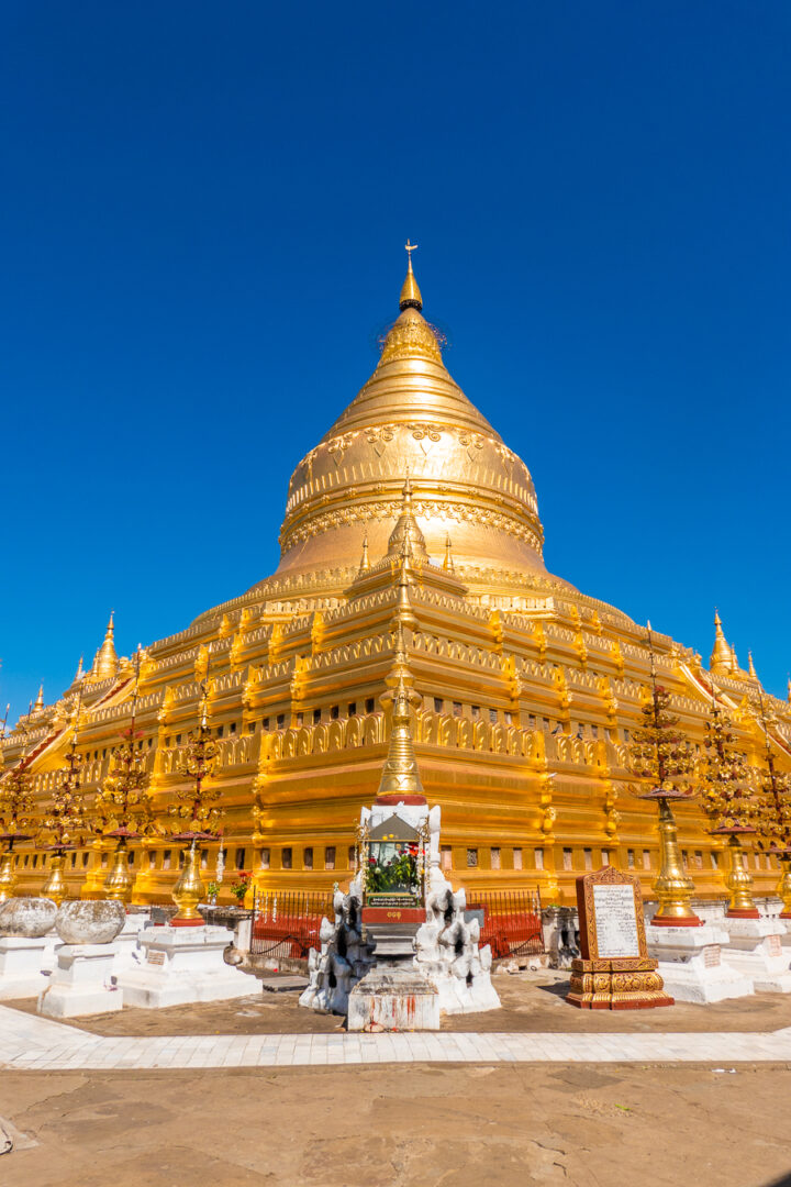 Gold plated Shwezigon Pagoda in Bagan, Myanmar framed by the deep blue cloudless sky.