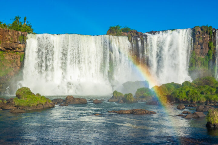 Photo of Iguazu Falls from Brazil with a rainbow in the mist.