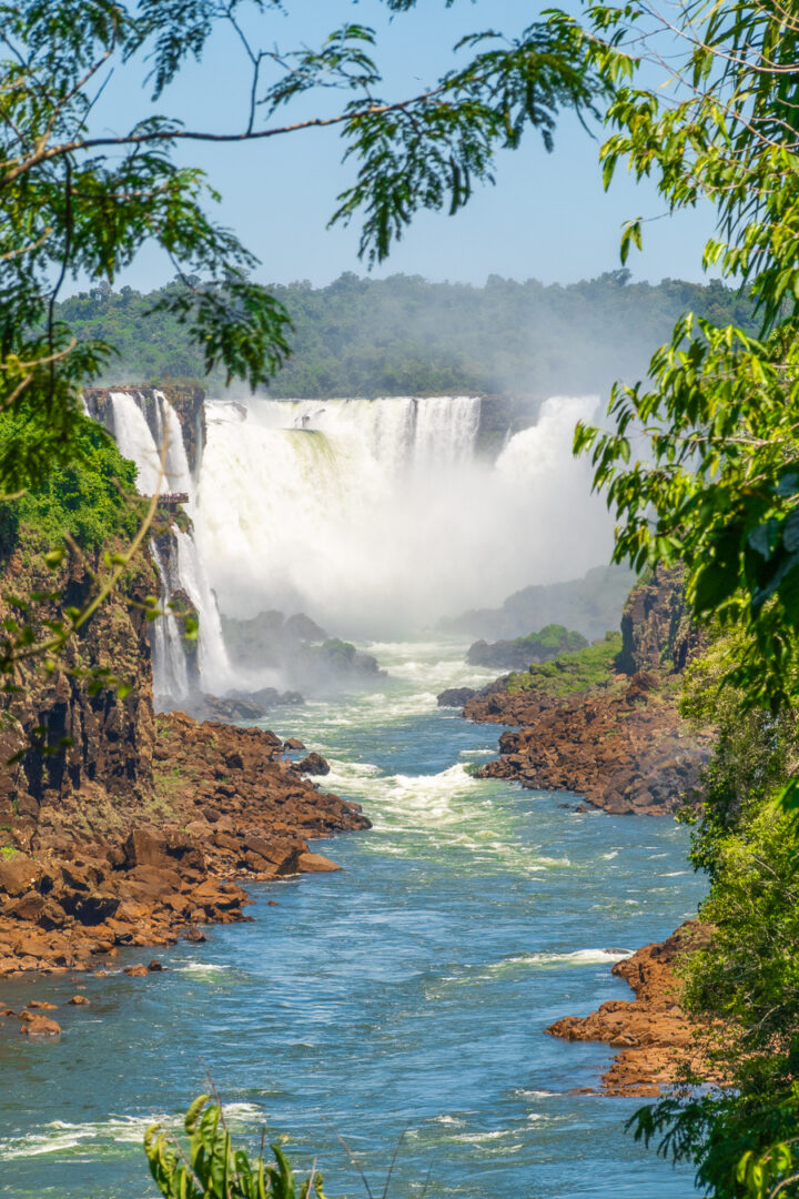 View of Iguazu Falls through trees from Argentina.