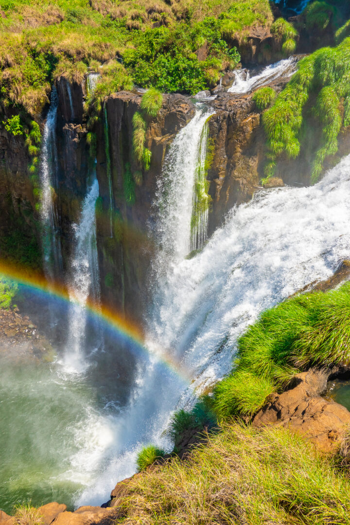 View of Iguazu Falls from Argentina with a rainbow in the mist.