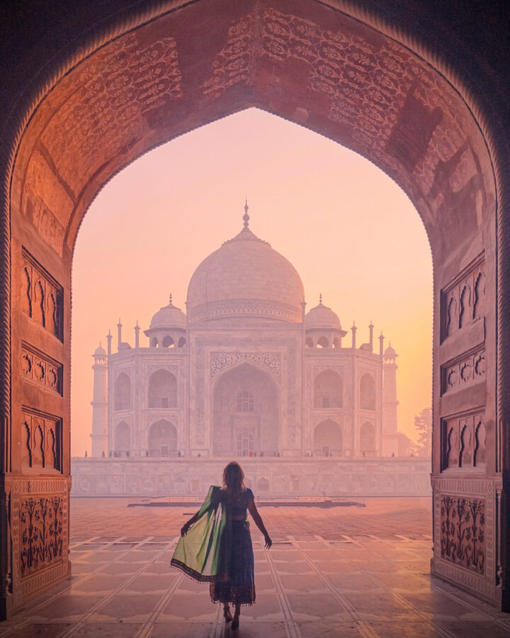 Amanda looking up at the Taj Mahal from under and archway in the early morning light.