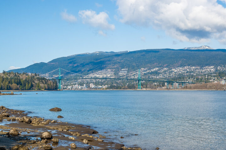 Lions gate bridge with mountains and city in background