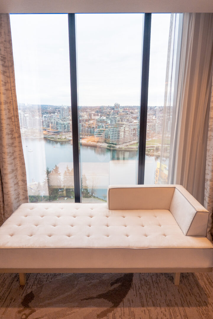 hotel room on a high floor with couch in front of floor to ceiling windows with harbor view