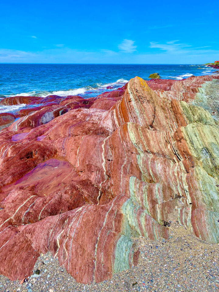 colorful red rock formations on beach in Gaspesie
