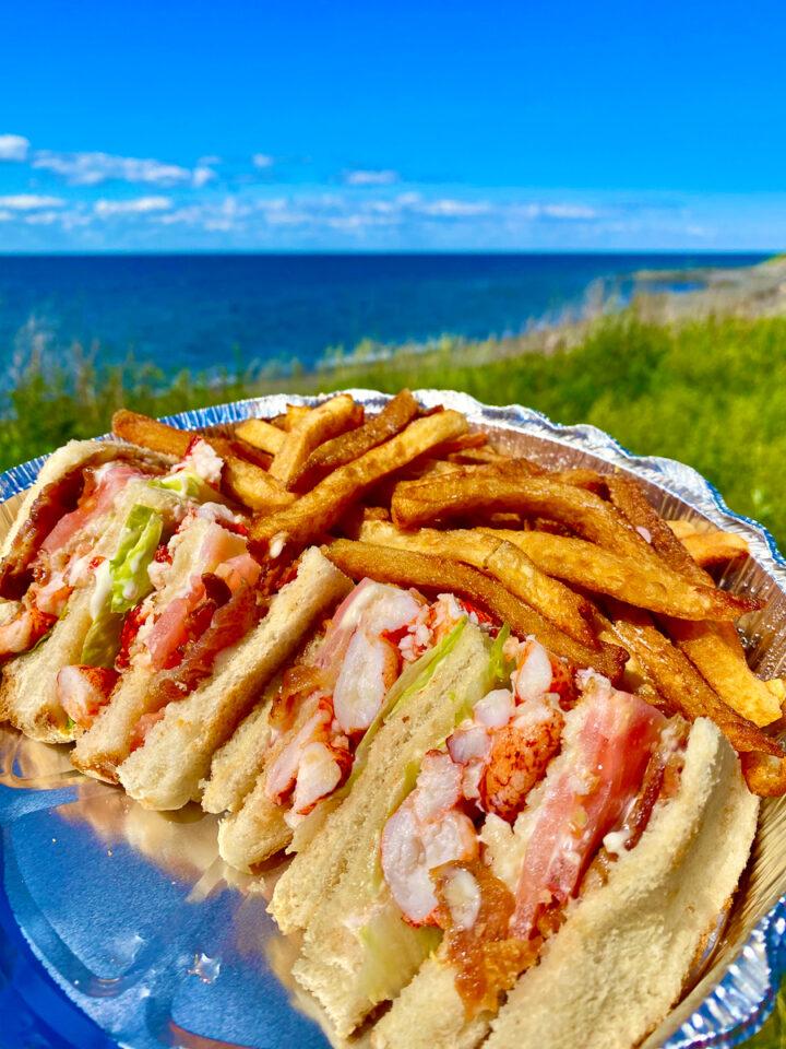 lobster club sandwich with poutine on the beach in Gaspesie