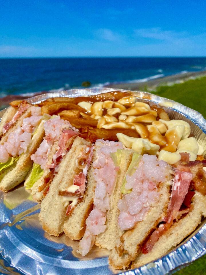 shrimp club sandwich with poutine on the beach in Gaspesie