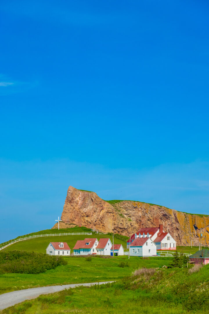 church with cross and red cliffs in perce quebec