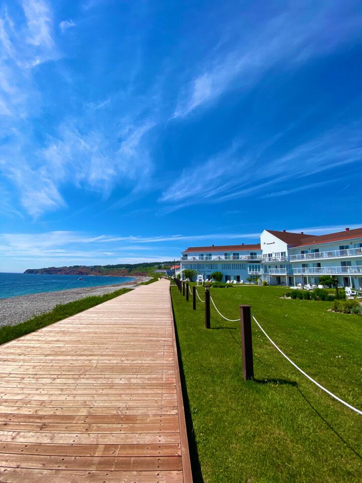 boardwalk in perce, quebec with la normandie hotel in background
